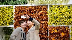 Dos chicas se hacen un selfi en una feria de flores en Japón.
