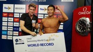 El nadador Jiayu Xu recibiendo el megatalón que certifica su récord del mundo.