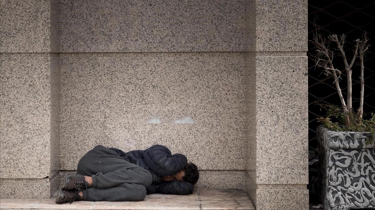 Un niño duerme en un portal, en la ciudad de Tánger.