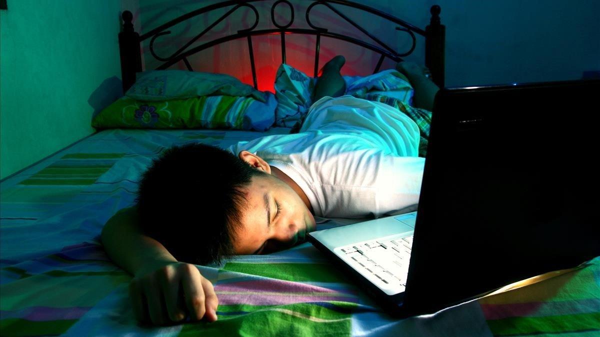 Un menor duerme frente a su ordenador, en una imagen de archivo