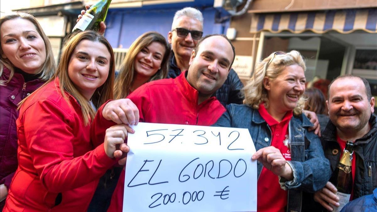 Varios premiados sostienen un cartel con el número del Gordo en Quintanar de la Orden.