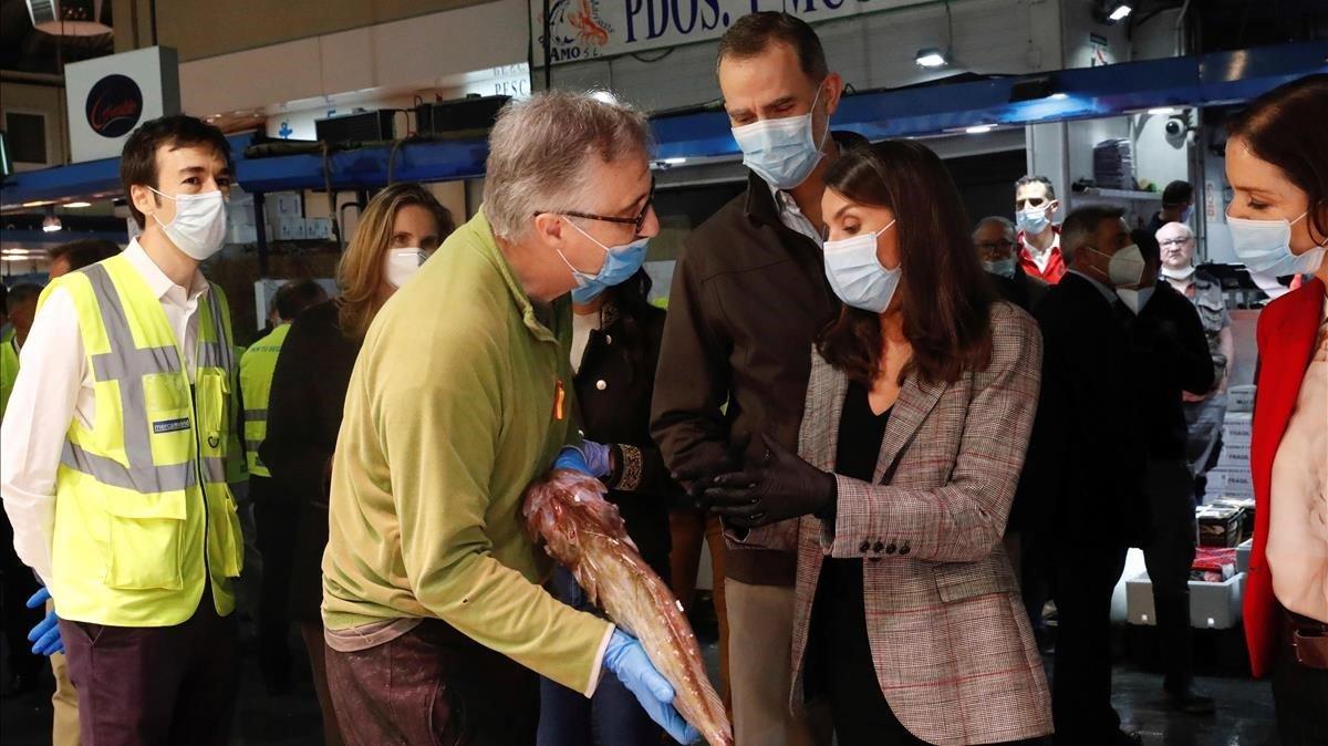 Don Felipe y doña Letizia conversan con un trabajador de Mercamadrid durante su recorrido por los puestos de aliemntso frescos.