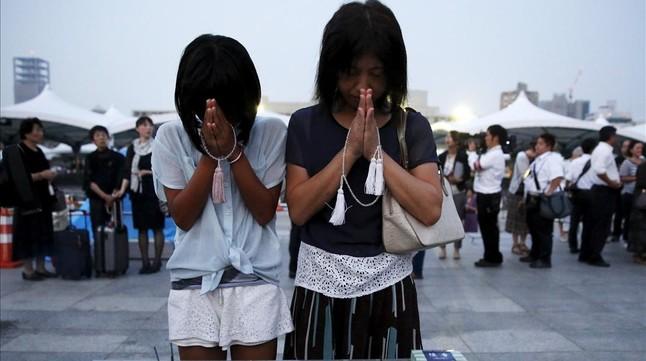 Una madre y una hija oran en el Parque Memorial de la Paz.
