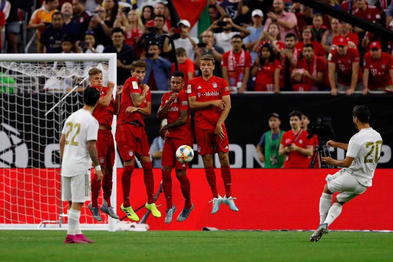 El madridista Marco Asensio (d) lanza una falta durante el Bayern-Real Madrid.