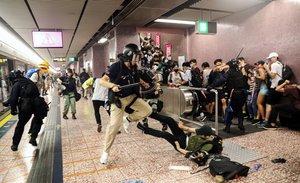 Agentes de policía cargan contra ciudadanos que venían de la manifestación, en la estación de metro Prince Edward de Hong Kong, este sábado.