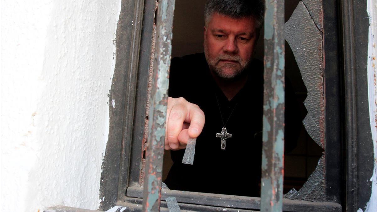 Un sacerdote evalúa los daños ocasionados en una de las iglesias atacadas durante la visita del Papa a Chile.