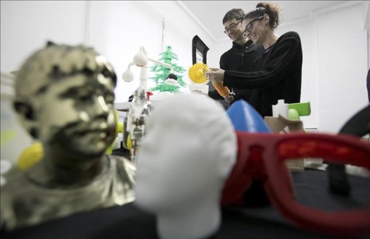 Al fondo, los hermanos Torras, Marc y María, en la sede de EntresD, rodeados por algunas de las piezas que han salido de sus impresoras.