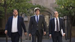 El president Carles Puigdemont, entre el vicepresidente Oriol Junqueras y el conseller Jordi Turull, en el Palau de la Generalitat.