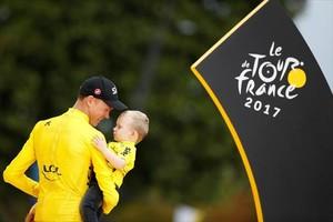 Chris Froome, el ciclista británico, sostiene en brazos a Kellan, su hijo, en el podio de París, en el 2017.
