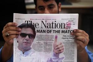 Un ciudadano lee un periodico que lleva a su portada una foto del exjugador de criquet Imran Khan lider del partido Pakistan Tehreek-i-Insaf .PTI