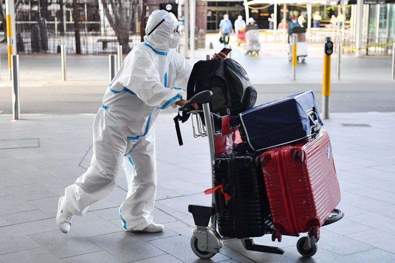 Un viajero viste un traje protector a su llegada al aeropuerto de Sidney, Australia.
