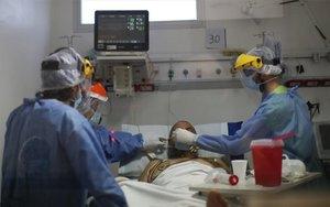 Personal médico atienden a enfermo de COVID-19 en Argentina.