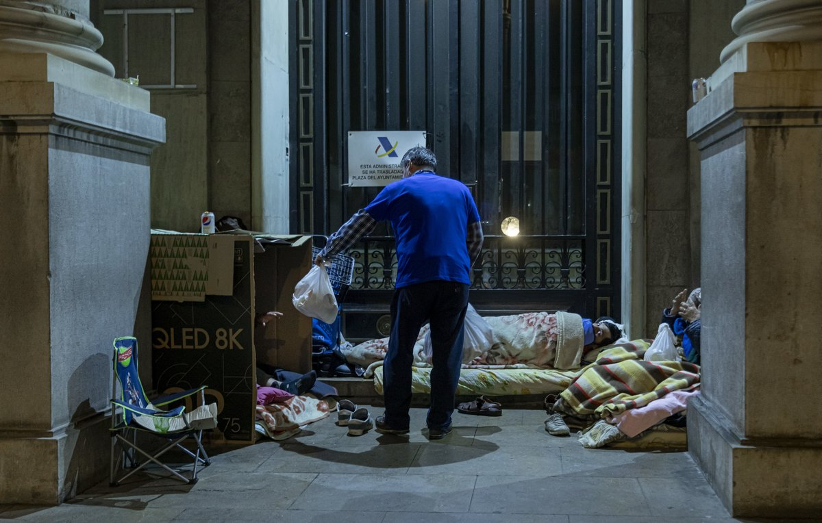 Confinados en la calle. Un voluntario reparte comida a personas sin hogar durante el estado de alarma.