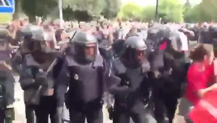 La Policia Nacional carga contra un cordón de seguridad realizado por efectivos del cuerpo de Bombers de la Generalitat frente a un colegio electoral.