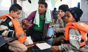Fotografia cedida por la ONG Sea-Watch que muestra a Nasreen 2d y a su hijo Zizou i junto a otros inmigrantes a bordo del buque Sea Watch 3 en el mediterraneo el 23 de diciembre de 2018.