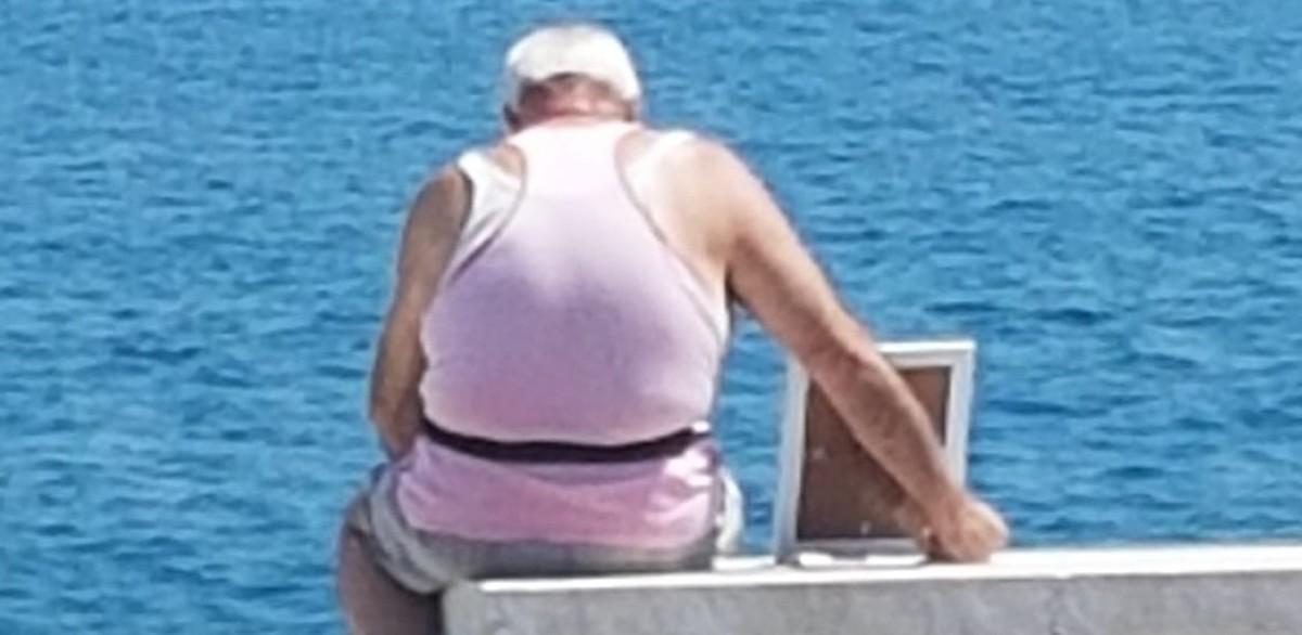 La historia del anciano que llora frente al mar junto a la fotografía de su difunta esposa