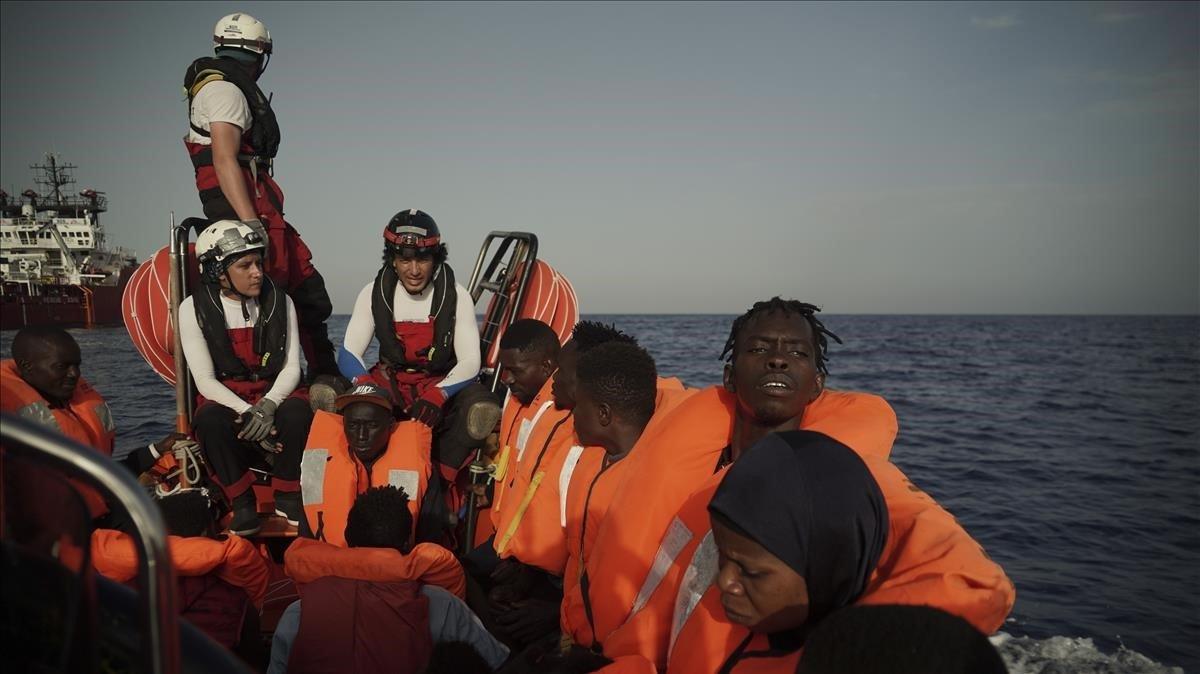 Un grupo de migrantes rescatados en el Mediterráneo son llevados al 'Ocean Viking', este miércoles.