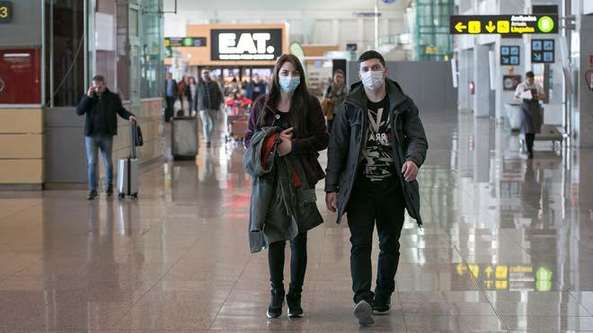 Ya hay siete pacientes en España contagiados con el coronavirus. En la foto, pasajeros con mascarillas en el aeropuerto de El Prat.