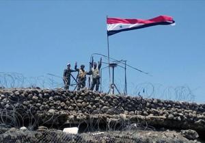 Las tropas gubernamentales muestran el signo de la victoria al lado de la bandera siria en Daraa.