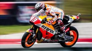 Marc Márquez sobre su Honda, con la moto enfocada hacia un lado y él balanceando su cuerpo hacia otro.