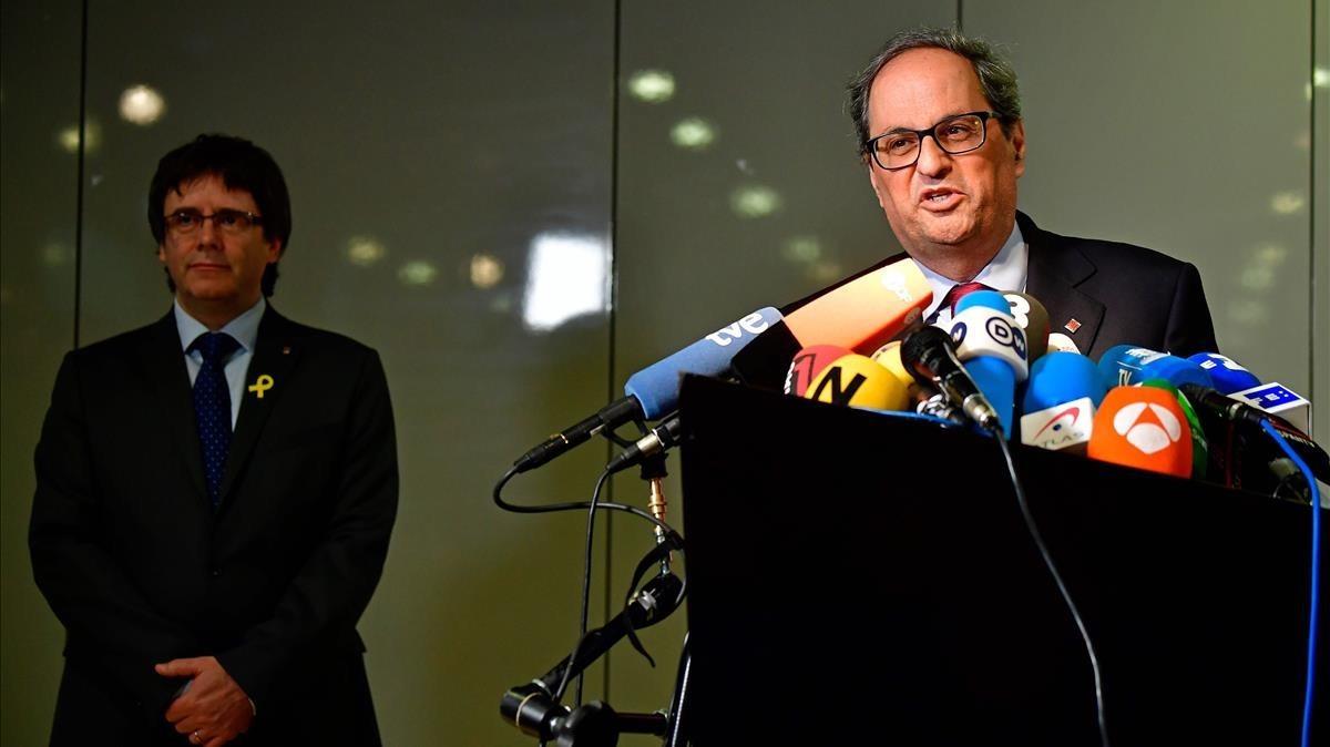 Quim Torra, en primer plano, y Carles Puigdemont, al fondo, en la rueda de prensa en Berlín.