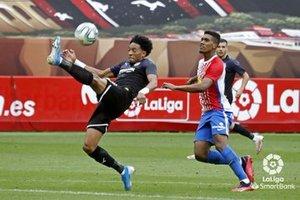 Mojica despeja un balón presionado por un jugador del Sporting.