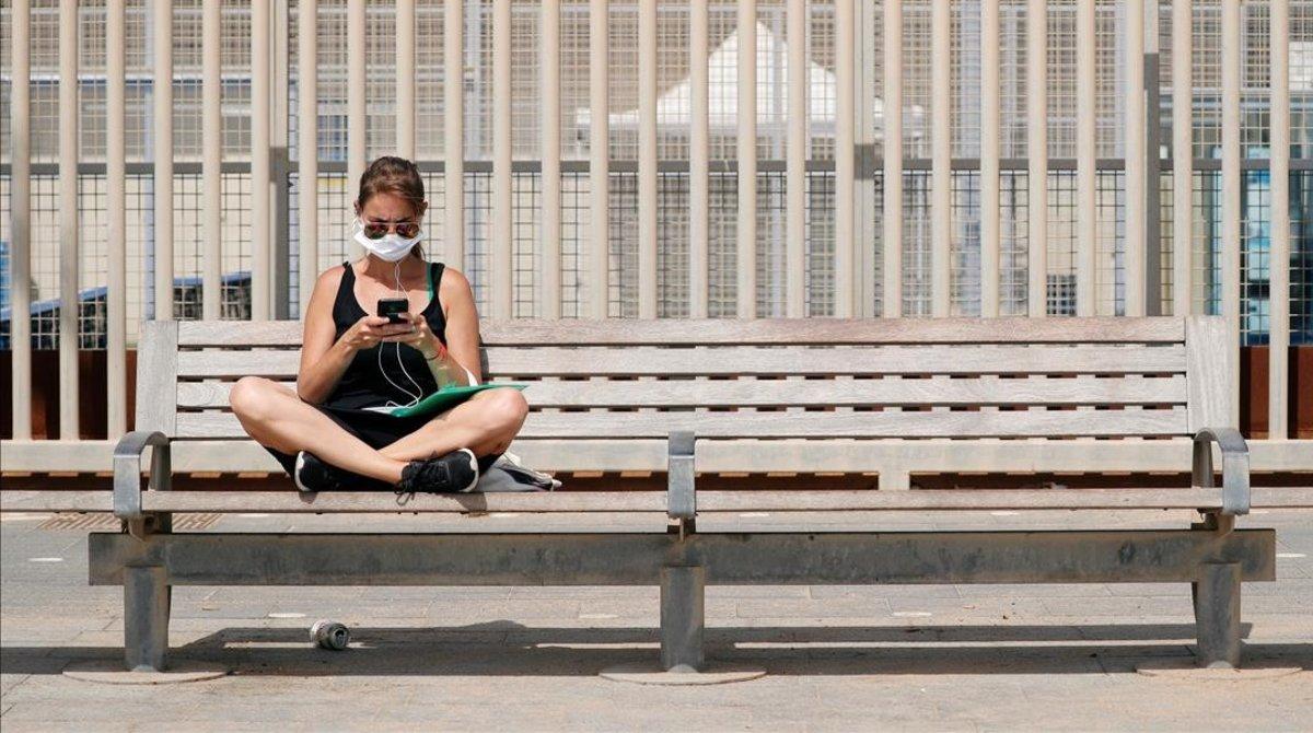 Una mujer, con mascarilla por el coronavirus, en un banco de Barcelona.