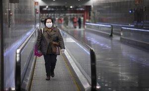 Una mujer con mascarilla para protegerse del coronavirus en la estación de metro de Diagonal, en Barcelona.