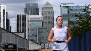 Una mujer corre por el distrito financiero de Londres, cuyas oficinas siguen vacías de trabajadores.