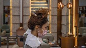 Una mujer se protege con una máscara en su visita a una peluquería de la ciudad china de Wuhan.