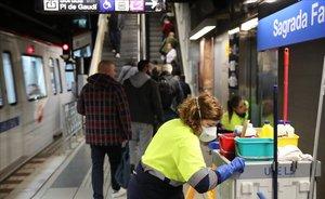 Una operaria de la limpiea con mascarllla trabaja en la estación de metro de Sagrada Família.