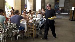 Un camarero sirve a un grupo de clientes en una terraza de Barcelona.