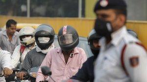 Varios motoristas y un guardia se protegen con mascarillas de la elevada polución, este lunes en Nueva Deli.