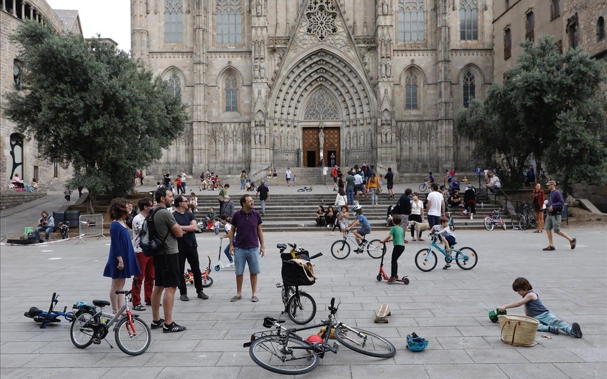 Vecinos con bicicletas frente a la catedral de Barcelona, sin turistas.
