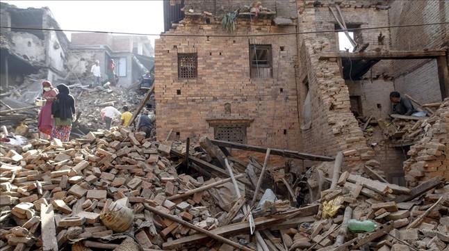 Veïns de Bhaktapur busquen pertinences entre les seves cases destruïdes pel terratrèmol, aquest dilluns.