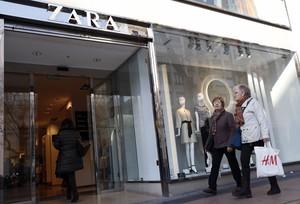 Mujeres pasean con una bolsa del H&M frente a una de las tiendas del Zara que hay en el centro de Madrid