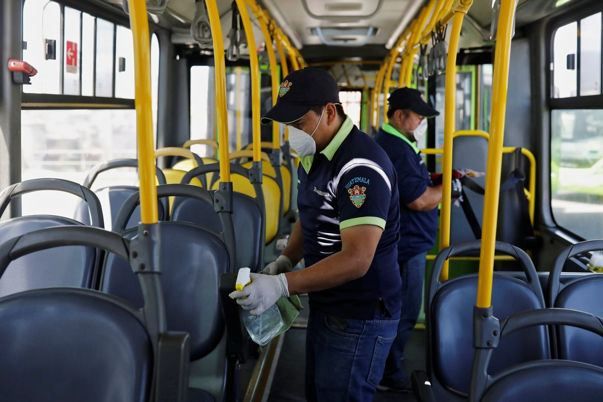 Workers wearing protective face masks clean the interior of a public bus, amid concerns over the spread of coronavirus disease (COVID-19), in Guatemala City, Guatemala March 15, 2020. REUTERS/Luis Echeverria