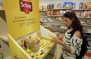 Una mujer compra productos para celíacos en una tienda