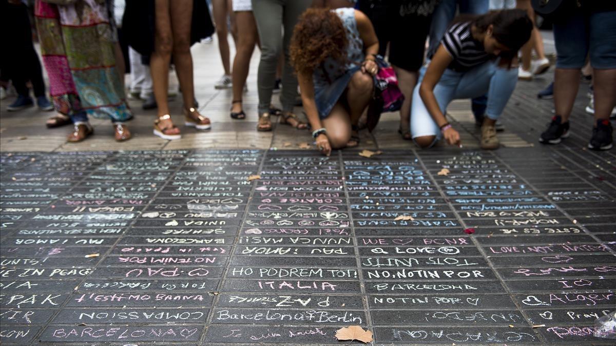 Los transeúntes escriben sus condolencias con tizas sobre el pavimento de la Rambla.