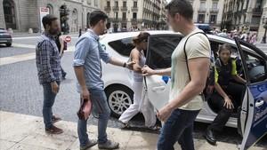 Agentes de paisano de la Guardia Urbana se llevan a una carterista detenida en la plaza de Sant Jaume.