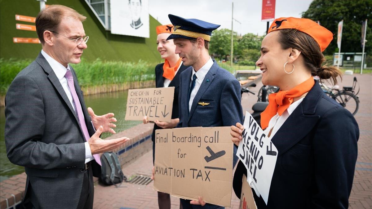 Activistas ambientales abordan a los participantes de la conferencia de La Haya sobre nuevos impuestos a la aviación.