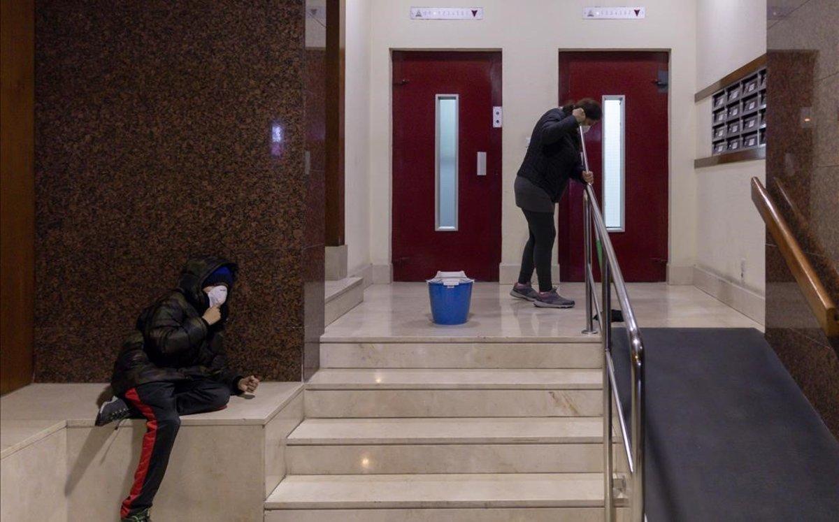 Una trabajadora de la limpiezaacompañada por su hijo.