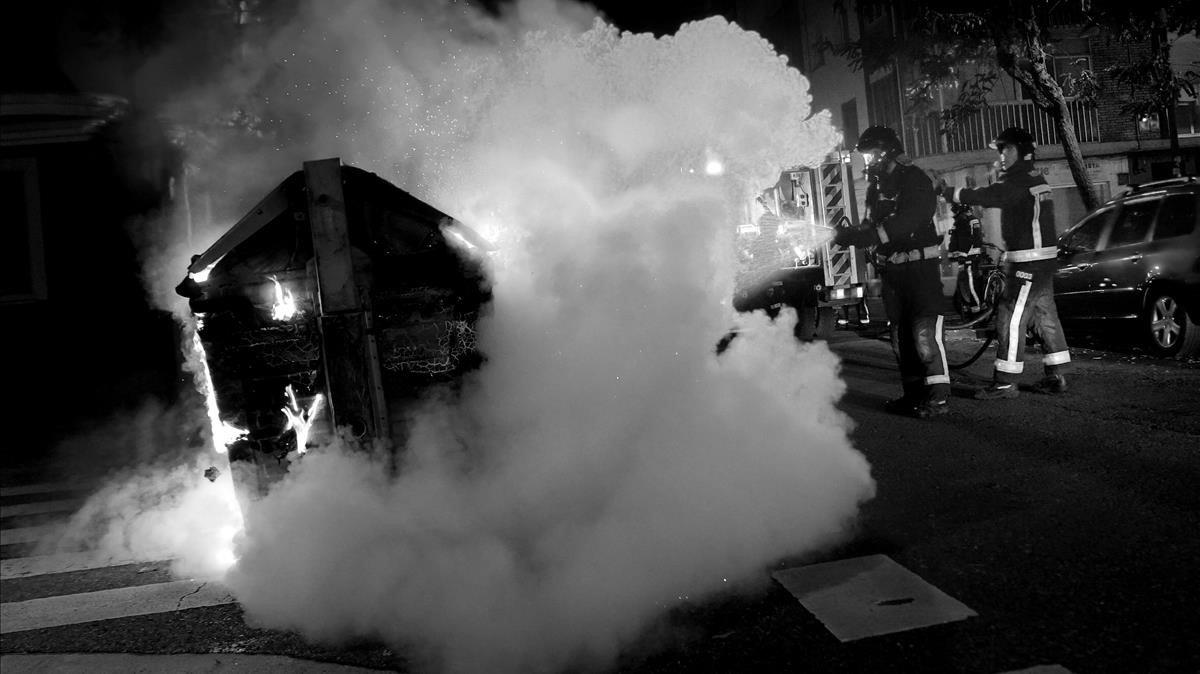 Un bombero apaga un contenedor de basura incenciado durante las protestas en Burgos.