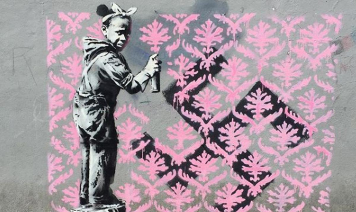 Obra de Banksy en que una niña negra intenta tapar una cruz gamada.