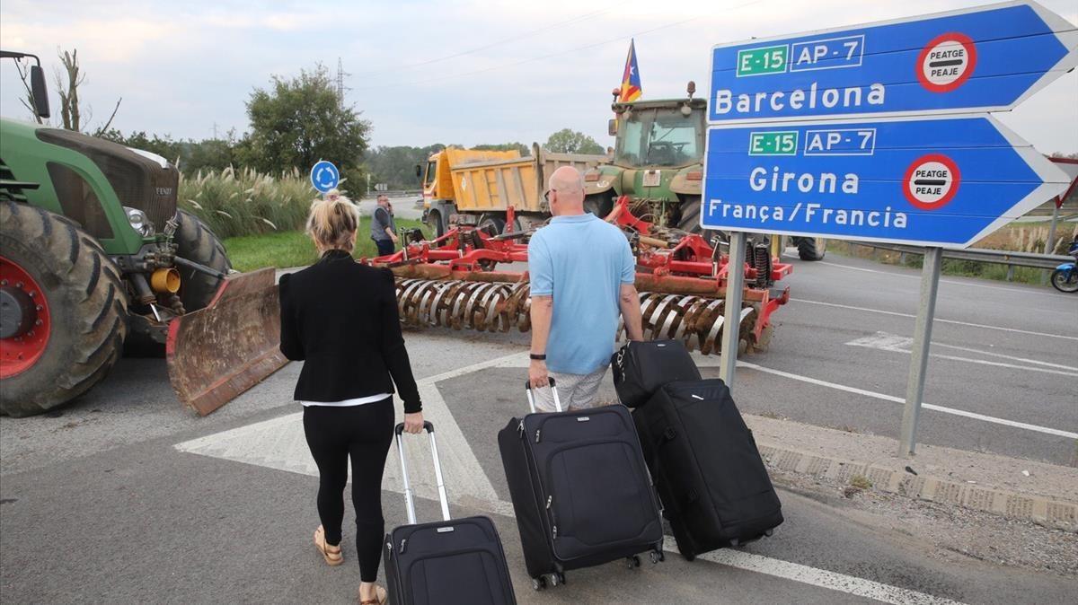 El acceso al aeropuerto de Girona, en Riudellots de la Selva, permanece cortado por el día de paro. Aquellos que desean viajar deben llegar a pie al aeropuerto.