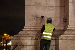A Yellow vestsGilets jaunesanti-government protester scrawls graffiti that readsMacron resignon the wall of the Arc de Triumph in central Paris.Photo by Zakaria ABDELKAFIAFP