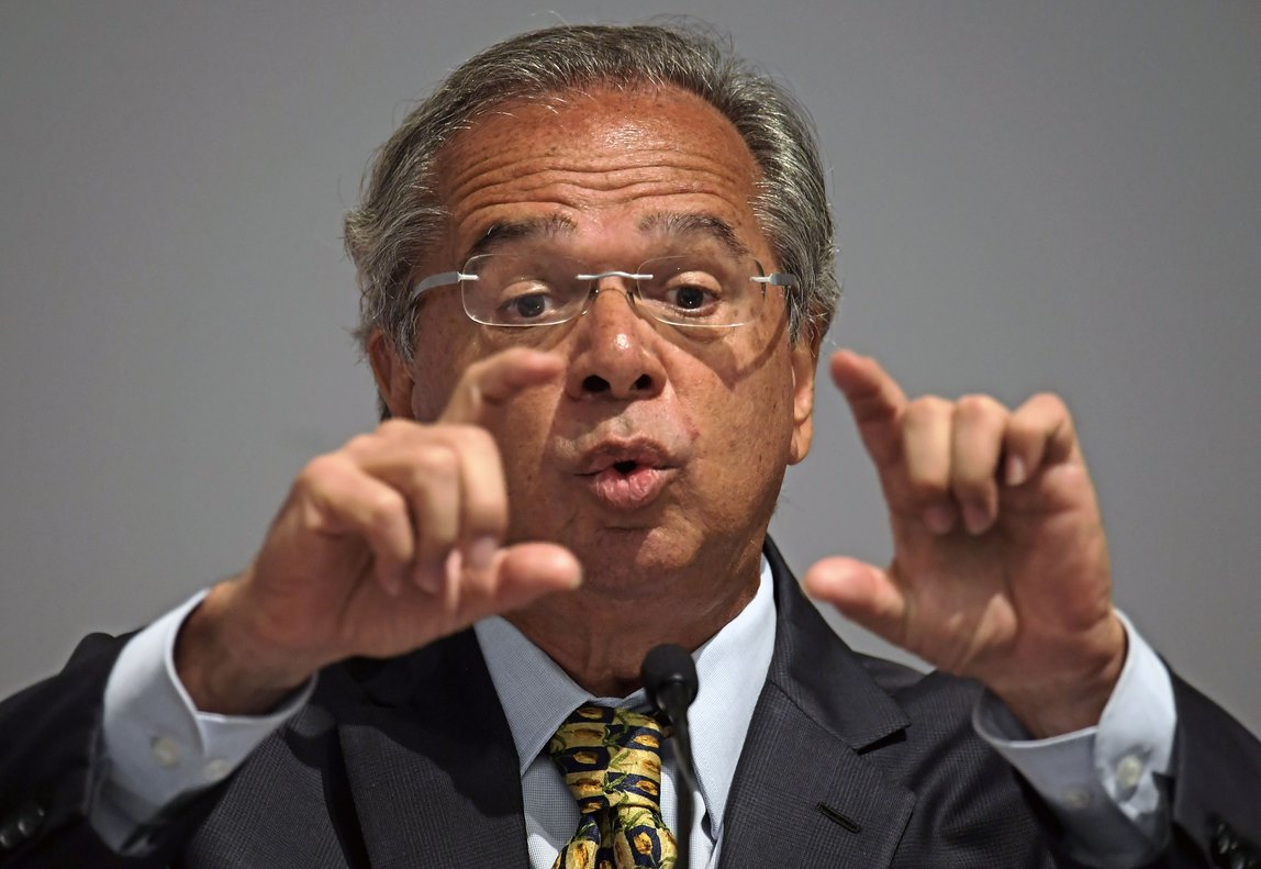 Brazl s President Jair Bolsonaro has appointed a free-marketeer  Paulo Guedes  as economy minister to push through reforms to bring down Brazil s swelling debt  mainly through privatizations  tax changes and encouraging foreign investment   Photo by CARL DE SOUZA   AFP