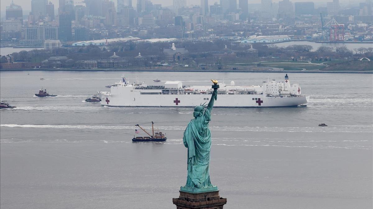 USNS Comfort, un barco hospital de la Marina de EEUU, pasa el lunes 30 de marzo de 2020 junto a la Estatua de la Libertad en su entrada a Nueva York. Con capacidad para 1.000 camas y 1.200 militares sanitarios, ayudará a aliviar otros hospitales que luchan contra el coronavirus.