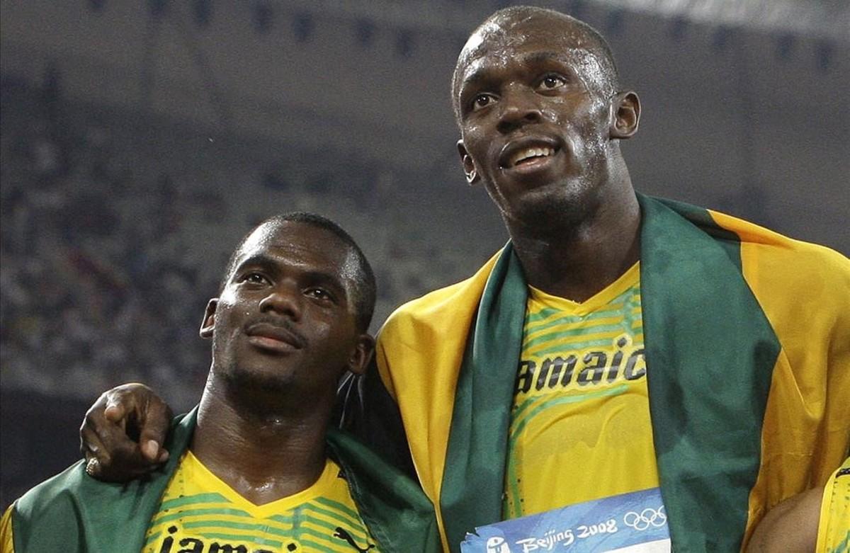 Bolt posa con Carter después de su triunfo en la final del relevo de Pekín