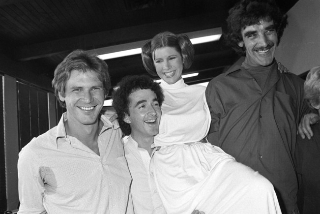 FILE - In this Oct. 5, 1978 photo, from left, actors Harrison Ford, Anthony Daniels, Carrie Fisher and Peter Mayhew take a break from filming a television special in Los Angeles to be telecast during the holidays. On Tuesday, Dec. 27, 2016, a publicist says Fisher has died at the age of 60. (AP Photo/George Brich, File)